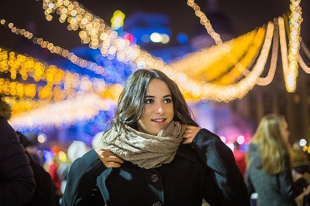 Woman standing in front of fairy lights