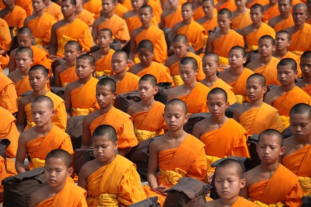thai monks sitting in prayer