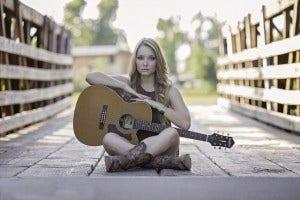 female guitarist sits on bridge