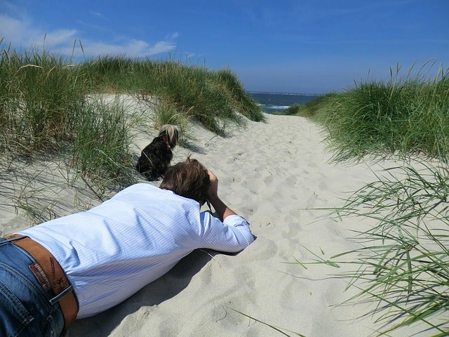 A man taking a photo in the sand