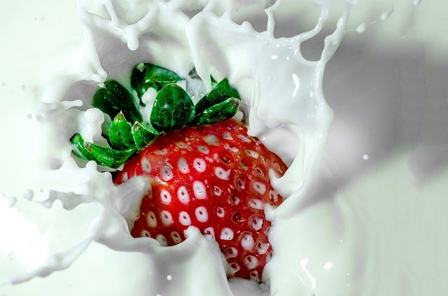 Strawberry splashing into some milk