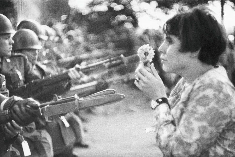 hippy-anti-vietnam-war-protester-shows-flower-to-national-guardsmen