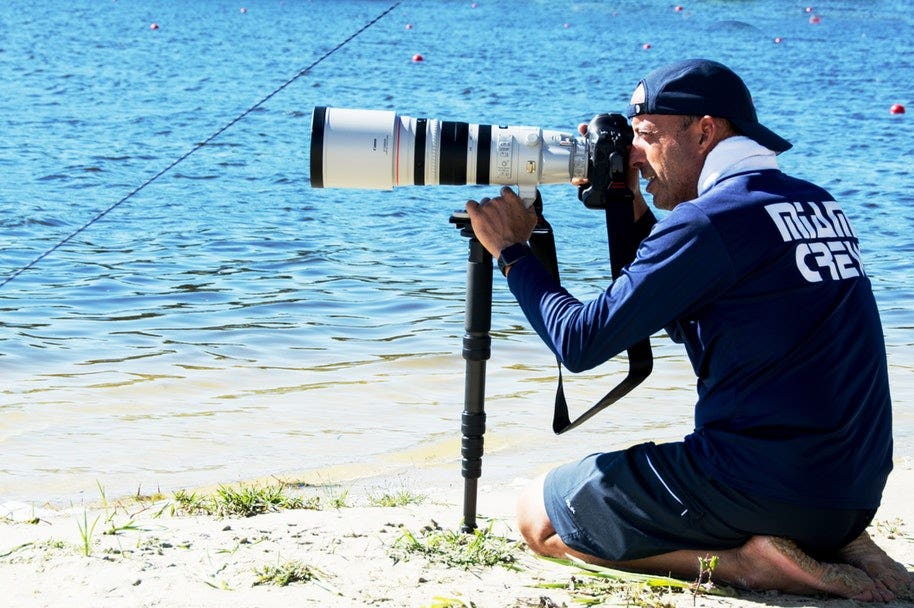 sports photographer on beach pointing camera at waves