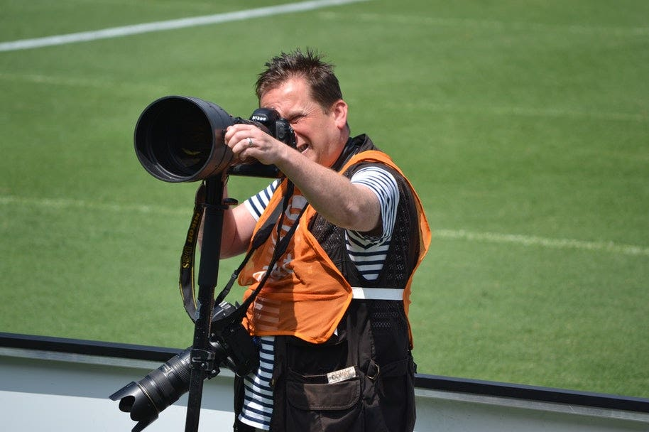 sports photographer holding camera with with zoom lens