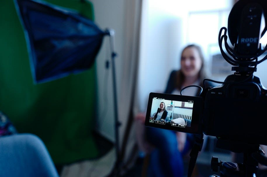 video shoot with camera pointed at woman in chair
