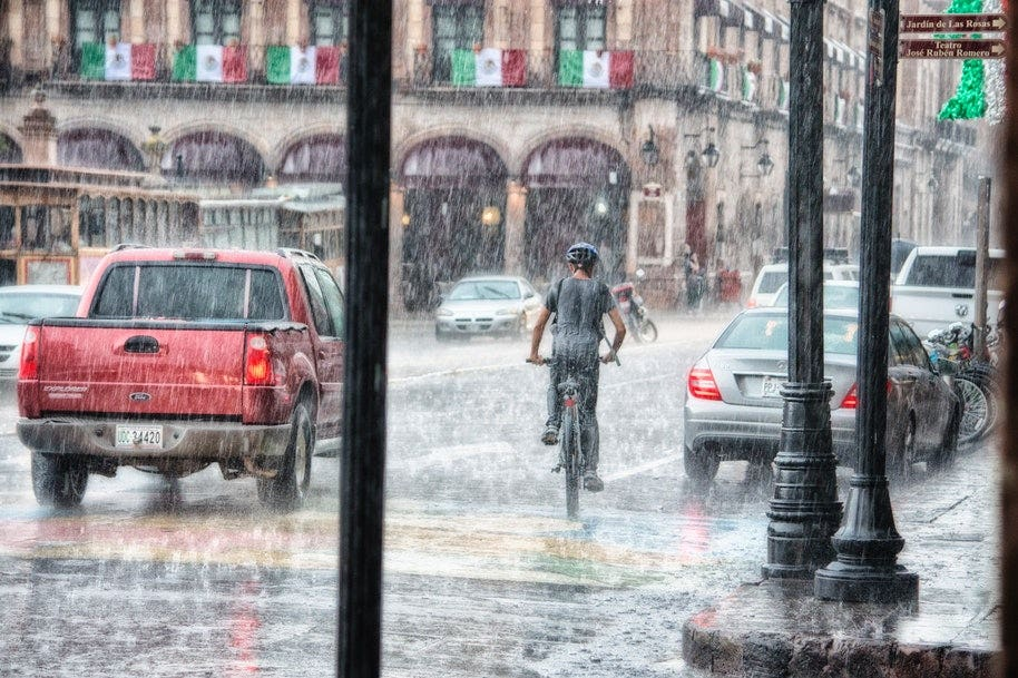 person riding bike in rain