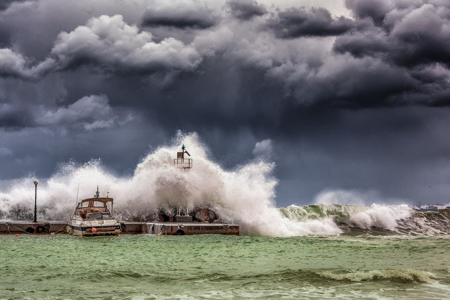 waves crashing onto lighthouse in storm