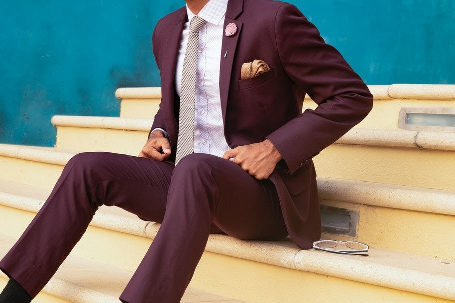 A man wearing formal suit and sitting on stairs.