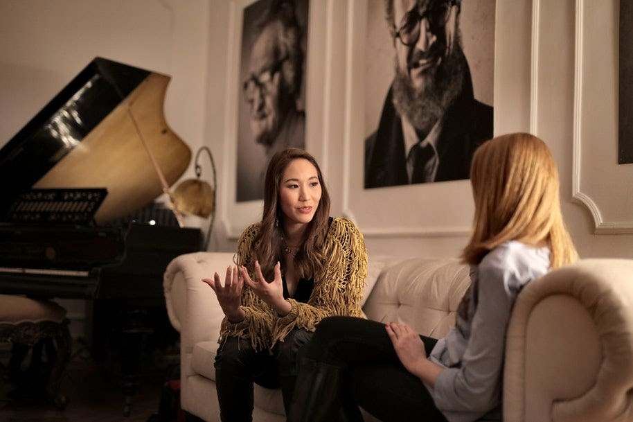 two women talking on a couch in a video interview.