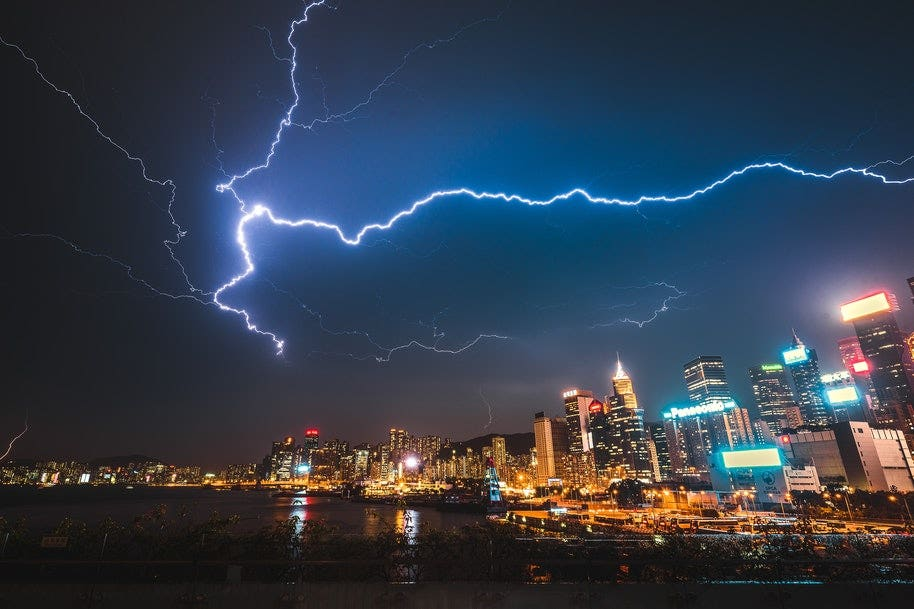 Lightning over city skyline and water.