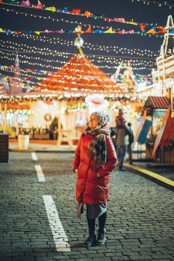 Woman looking at Christmas lights in street.