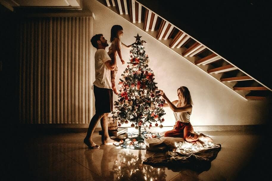 A father holding up his daughter to put the star on the Christmas tree