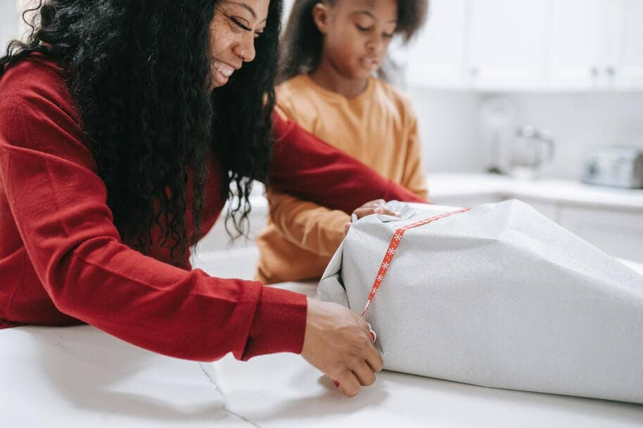 A mother wrapping a Christmas present with her child.