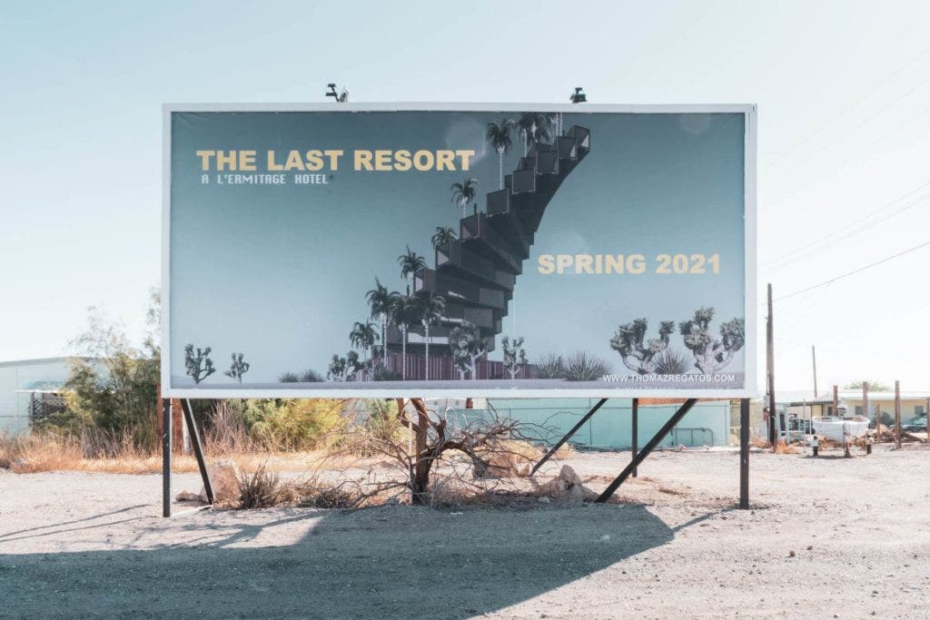 A large billboard in the desert advertising a hotel.