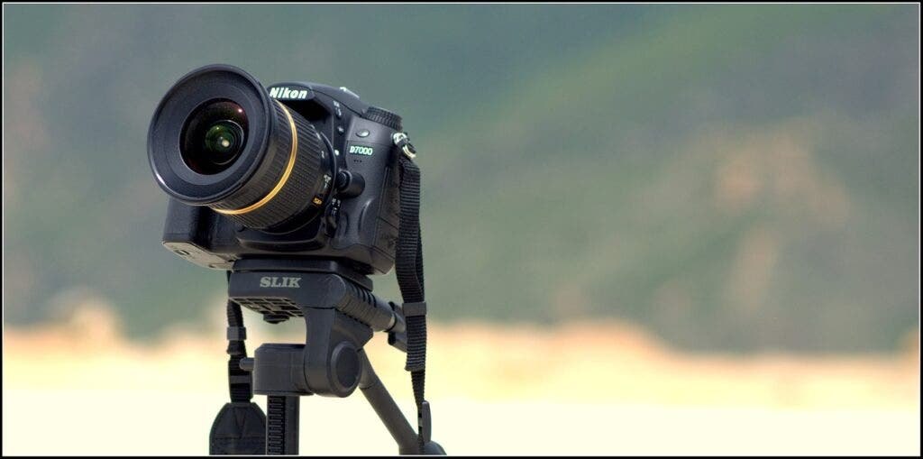 Tamron lens on a Nikon camera on a tripod with a landscape in the background.